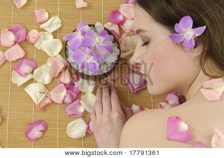 Beautiful sleeping girl in rose petal with bowl of salt-Spa resort