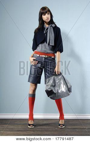 Fashion girl with handbag posing in the studio
