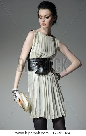 Fashion girl holding little purse shot in studio