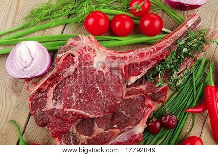 fresh spare ribs : raw lamb with thyme , red chili pepper , tomato , garlic , and chives over wooden table