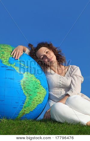 young woman sitting near big inflatable globe on summer lawn