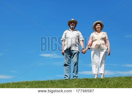 old man and woman in straw hats standing on hill and holding for hands, blue sky and green lawn