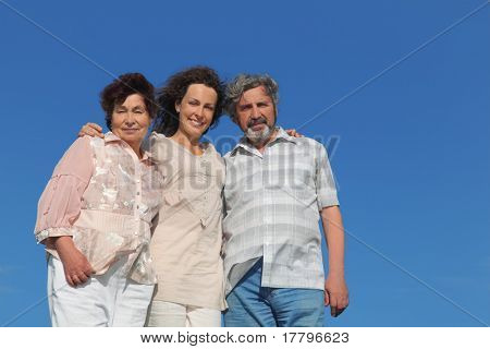 portrait of adult daughter and her parents embracing and smiling, blue sky