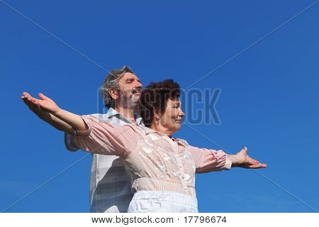 old man and woman standing, smiling and looking at side, hands apart, blue sky