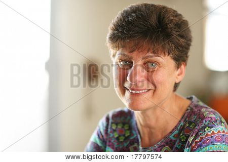 Portrait of happy mature woman at home. Closeup, shallow DOF.