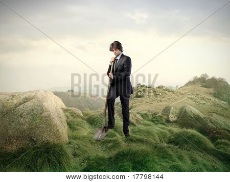 Businessman digging with a shovel in the mountains