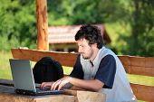 image of online education  - College student working on a laptop in the park - JPG