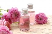 bottles with essential oil and pink dahlia flower on woven mat