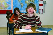 image of students classroom  - A teenage boy listens with attention to a school lesson in high school classroom - JPG