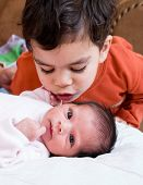 foto of east-indian  - A young boy talking to his newborn sister - JPG