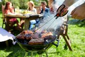 leisure, food, people and holidays concept - man cooking meat on barbecue grill for his friends at s poster