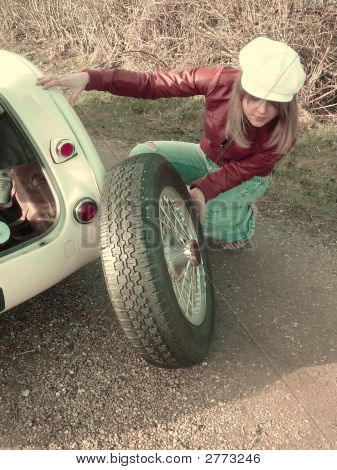 Retro Girl Changing Tire On Car