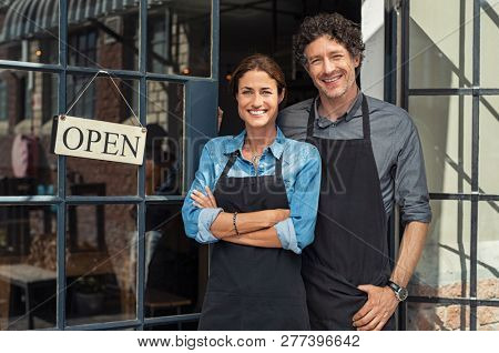 poster of Two cheerful small business owners smiling and looking at camera while standing at entrance door. Ha