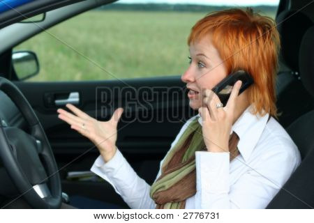 Red-Haired Woman With Mobile-Phone In A Car. She Is Fury