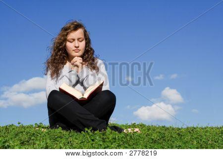Criança lendo Bíblia e orando