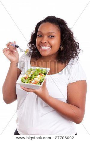 Joven mujer afroamericana comer ensalada