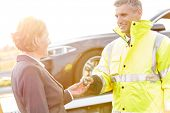 Smiling tow truck driver giving car key to businesswoman poster