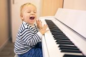 Sweet Positive Toddler Child Playing Piano. Early Music Education For Little Kids. poster