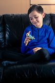 8 Year Old Boy Wearing Sportive Clothing Looking At His Asthma Inhaler Sitting In Sofa. Concepts : H poster