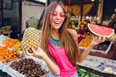 Girl With Long Hair In Pink Sunglasses Having Fun On Market With Tropical Fruits. She Holds Slice Of poster
