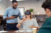 Mature executive man holding tablet showing video to woman wearing virtual glasses at office. Happy  poster