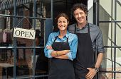 Two cheerful small business owners smiling and looking at camera while standing at entrance door. Ha poster