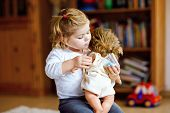 Adorable Cute Little Toddler Girl Playing With Doll. Happy Healthy Baby Child Having Fun With Role G poster
