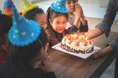 Group Of Children Is Blowing Birthday Cake In Birthday  Party Singing Happy Birthday poster