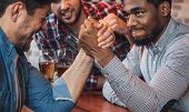 Male Friends Arm Wrestling Each Other, Drinking Beer In Bar poster