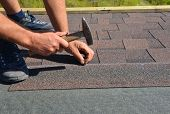 Roofer Installing Asphalt Shingles On House Roofing Construction With Hammer And Nails. Roofing Cons poster