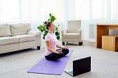 Girl Sitting In Lotus Position And Meditating At Home Interior, Copy Space. Padmasana. Woman Practic poster