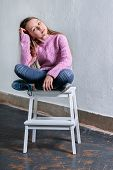 Stylish Child Girl Sitting Fashion Pose On Chair. Beautiful Glamorous Kid Teenager Model In Pink Swe poster