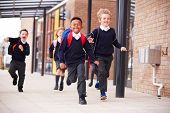 Happy primary school kids, wearing school uniforms and backpacks, running on a walkway outside their poster