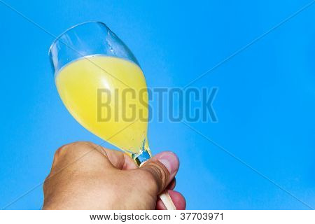 Holding A Glass Of Champagne Mixed With Orange Juice Against Blue Sky