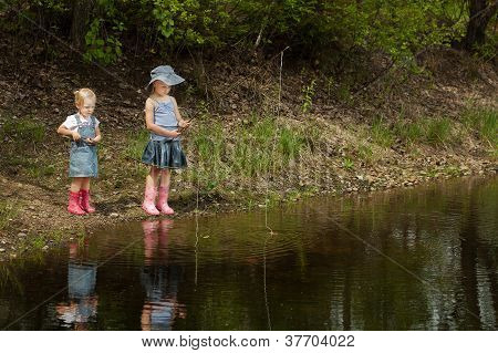Little Girls Are Fishing On Lake In Forest