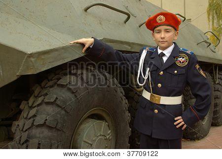 Menino de uniforme com uma companhia de tropas blindada