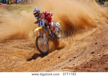 Motocross Rider Accelerating Out Of Corner Huge Roost In Tow