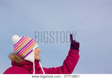 Pretty Girl In Witer Clothes Pointing Upwards