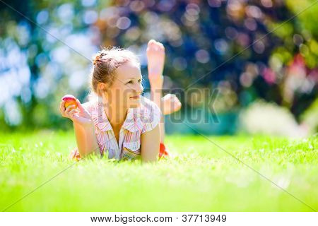 Girl with an apple on green grass