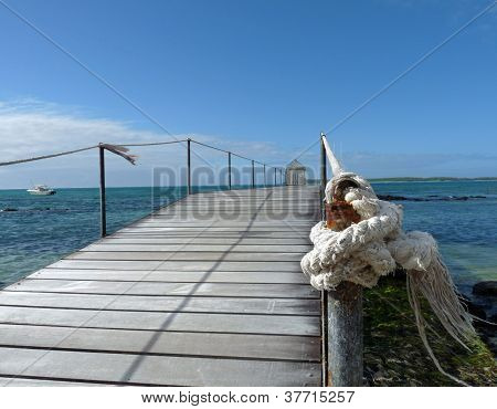 Close up of wooden jetty with knotted rope leading out towards the Indian Ocean