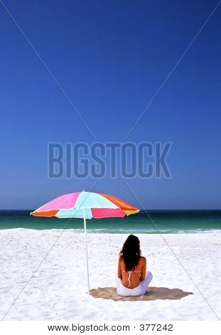 Woman Sitting On Spanish Beach Under Sun Umbrella. White Sand Blue Sea And Sky.