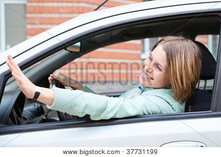 Pretty Young Blond Woman Waving Hers Hand Sitting In Car