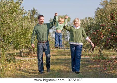 Parents Swinging Little Girl