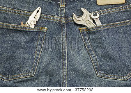 Working tools in old blue jeans pockets