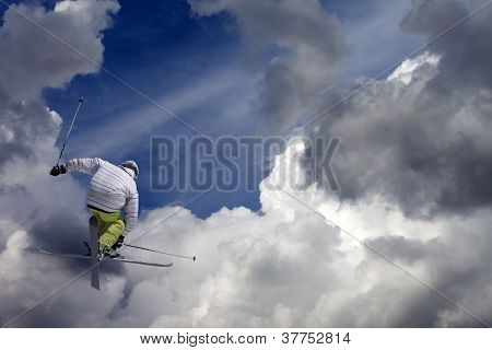 Freestyle Ski Jumper With Crossed Skis Against Blue Sky With Clouds