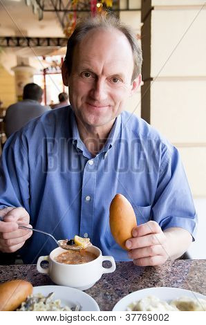 Happy aged man eating restaurant food
