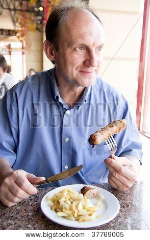 Happy aged man eating restaurant food