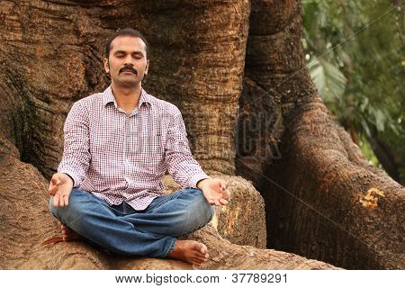 Close-up Photo Of A Handsome Indian Executive Doing Meditation Under A Tree In A Park. The Person Is