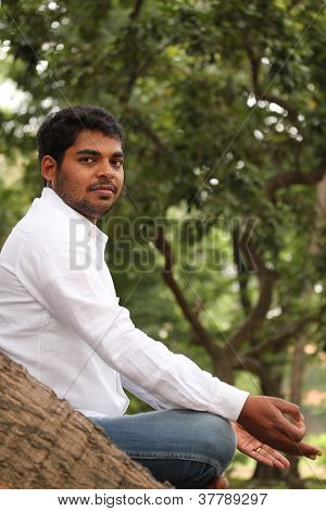 Close-up Profile Photo Of A Handsome Indian Man Meditating Under A Tree In A Garden. The Person Is S