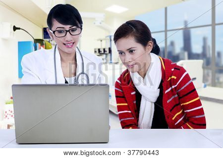 Doctor And Patient Looking At Laptop
